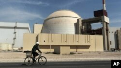 FILE - A worker rides in front of the reactor building of the Bushehr nuclear power plant, just outside Bushehr, Oct. 26, 2010.