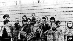 Sekelompok anak-anak berseragam kamp konsentrasi termasuk Martha Weiss yang berusia sepuluh tahun (nomor 6 dari kanan), di balik pagar kawat berduri di Oswiecim (Auschwitz), Januari 1945. (Foto: dok).