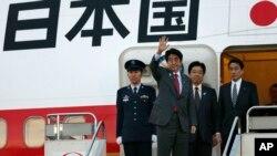 ນາຍົກລັດຖະມົນຕີຍີ່ປຸ່ນ ທ່ານ Shinzo Abe ໂບກມືສັ່ງລາ ໃນຂະນະທີ່ທ່ານຈະອອກເດີນທາງ ມາຍັງນະຄອນຫລວງ ວໍຊິງຕັນ ທີ່ເດີ່ນບິນສາກົນ Haneda ໃນກຸງໂຕກຽວ, ວັນທີ 21 ກຸມພາ 2013.