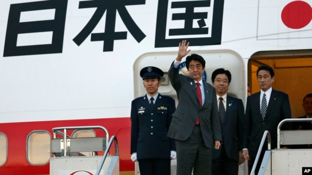 Japanese Prime Minister Shinzo Abe, second from left, waves before his departure for Washington at Haneda International Airport in Tokyo, February 21, 2013.