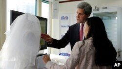U.S. Secretary of State John Kerry looks at a wedding dress created by Lihn Thai, front, founder and CEO of The One Couture, during a business event in Ho Chi Minh City, Vietnam Saturday, Dec. 14, 2013.