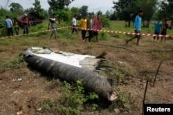 Warga setempat mendatangi lokasi ditemukannya kepingan pesawat turboprop ATR-72 yang jatuh di dekat Pakse, Laos (17/10).