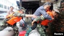 Cảnh sát bán quân sự cõng một phụ nữ ra khỏi một chiếc bè tại tỉnh Chiết Giang, Trung Quốc, ngày 8/10/2013.