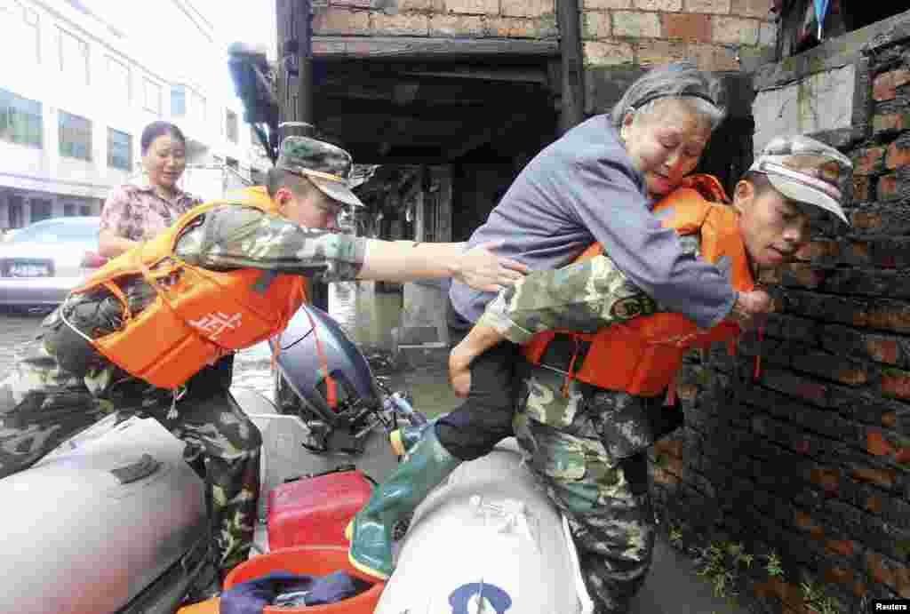 Paramilitary police carry an elderly woman off a raft as they rescue trapped residents after Typhoon Fitow hit Taizhou, Zhejiang province, China, Oct. 8, 2013.