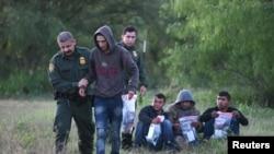 ARSIP - Agen-agen Patroli Perbatasan AS menangkap kaum migran yang tidak dilengkapi dokumen setelah melintasi perbatasan secara ilegal di perbatasan AS-Meksiko di Mission, Texas, AS, 9 April 2019 (foto: Reuters/Loren Elliott)