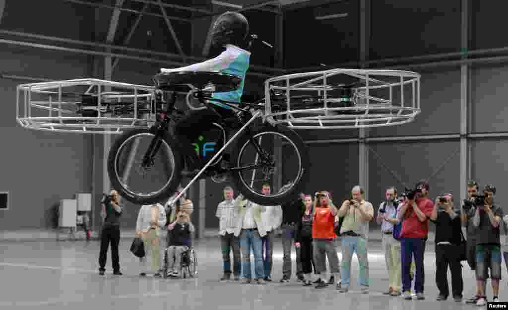 Journalists attend a presentation of a flying bicycle, carrying a dummy, at Letnany's fair hall in Prague, Czech Republic. The flying bicycle, which was created by Czech designers, is kept aloft by six electrically-powered propellers.