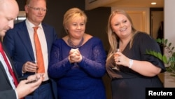Norway's Prime Minister Erna Solberg, her daughter Ingrid Solberg Finnes and Sgbjorn Aanes, Solberg's advisor react on the good results of Solberg's Conservative party Hoyre in Oslo, Norway, Sept. 11, 2017.
