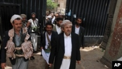 Yemeni tribal leader Sadiq al-Ahmar (C) is flanked by armed guards as he walks out of his residence in the al-Hasaba neighborhood of north Sana'a, May 26, 2011.