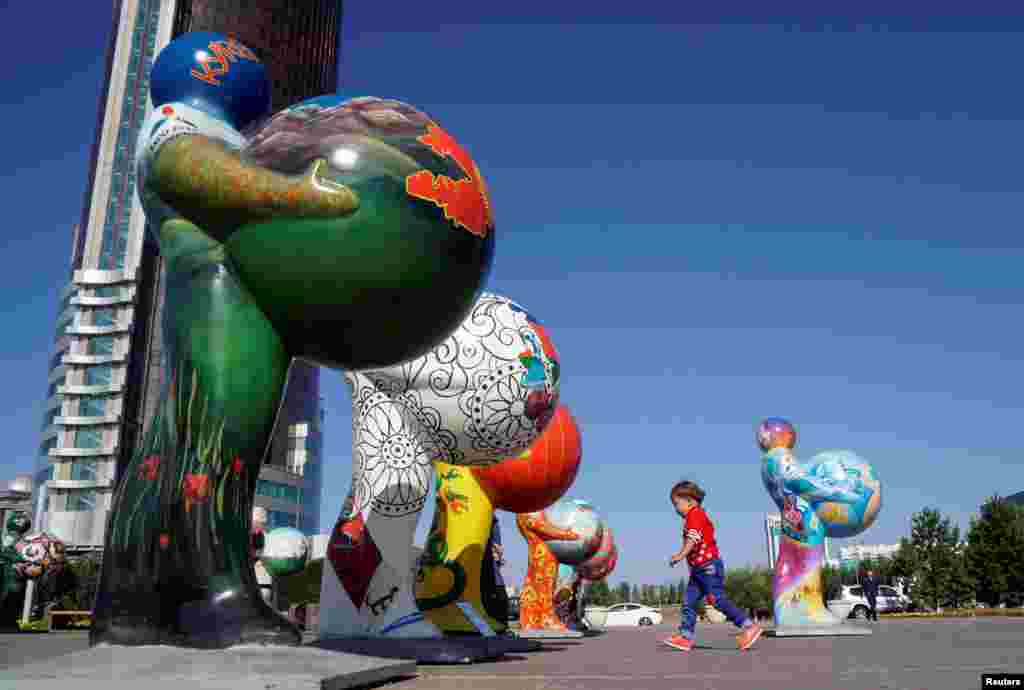 A boy runs past figures symbolizing countries participating in Expo 2017 at downtown of Astana, Kazakhstan. Astana will host the exhibition next year .
