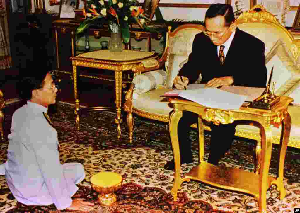 King Bhumibol Adulyadej grants an occasion to newly appointed Prime Minister Chuan Leekpai at the Royal Palace in Bangkok, Nov. 14, 1997.
