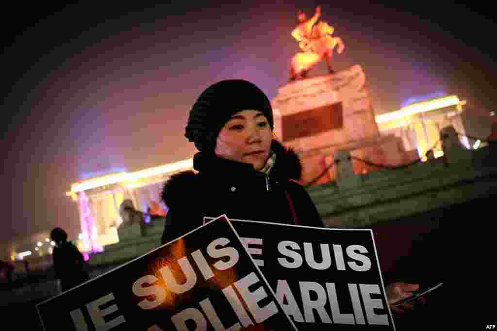 "A Mongolian journalist holds placards reading ""Je Suis Charlie"" (I am Charlie) as she takes part in a candlelight vigil with members of the French community and other Mongolian journalists at Chinggis Square in Ulan Bator, Jan. 9, 2015."