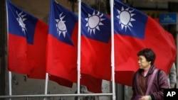 资料照:一名妇女走过台北街道旁飘扬的台湾旗帜。