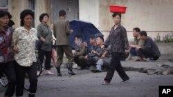 지난 6월 북한 원산의 한 도로 변에서 주민들이 담배를 피우고 있다.