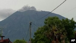 Gunung Agung mengeluarkan asap dan abu vulkanik dari kawahnya, terlihat dari Tulamben, Bali, Indonesia, 21 November 2017. (AP Photo/Wayan Wijaya)