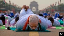 Indian Prime Minister Narendra Modi lies down on a mat as he performs yoga along with thousands of Indians on Rajpath, in New Delhi, India, Sunday, June 21, 2015. Millions of yoga enthusiasts are bending their bodies in complex postures across India as th