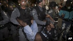 A protester, who is an Israeli Jews of Ethiopian origin, is carried by policemen during a demonstration against what they say is police racism and brutality, after the emergence last week of a video clip that showed policemen shoving and punching a black soldier in a protest at Rabin Square in Tel Aviv May 3, 2015.
