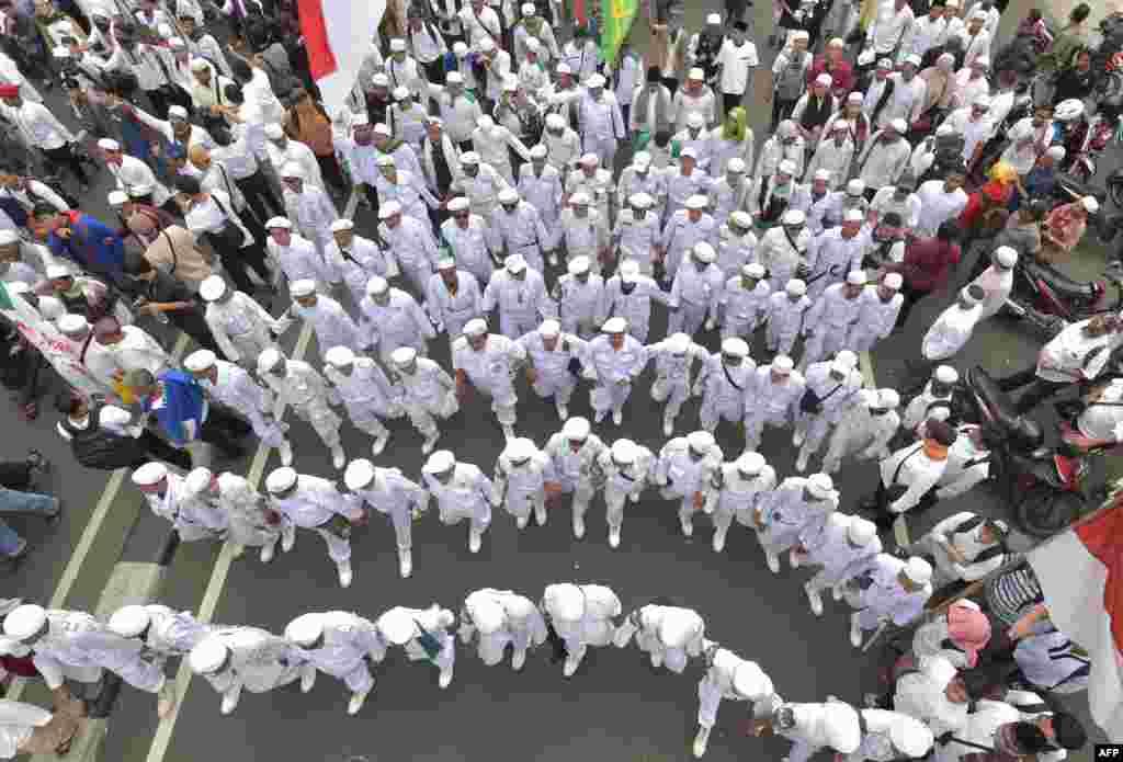 Kaum Muslimin Indonesia berbaris menuju istana presiden selama unjuk rasa menentang gubernur DKI Jakarta Basuki Tjahaja Purnama atas dugaan penghinaan di Jakarta.