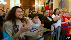Supporters of a bill to raise California's minimum wage celebrate outside the state Senate Chamber after the measure was approved by the Senate, March 31, 2016, in Sacramento, California. (AP Photo/Rich Pedroncelli)