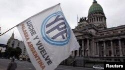 Un hombre agita una bandera con el logo de YPF en frente del congreso argentino, en Buenos Aires, donde esta maduraga de jueves fue aprobado el decreto de expropiación de YPF.