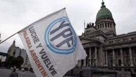 Un hombre agita una bandera con el logo de YPF en frente del congreso argentino, en Buenos Aires. Repsol ha puesto una demanda ante el Banco Mundial por este caso.