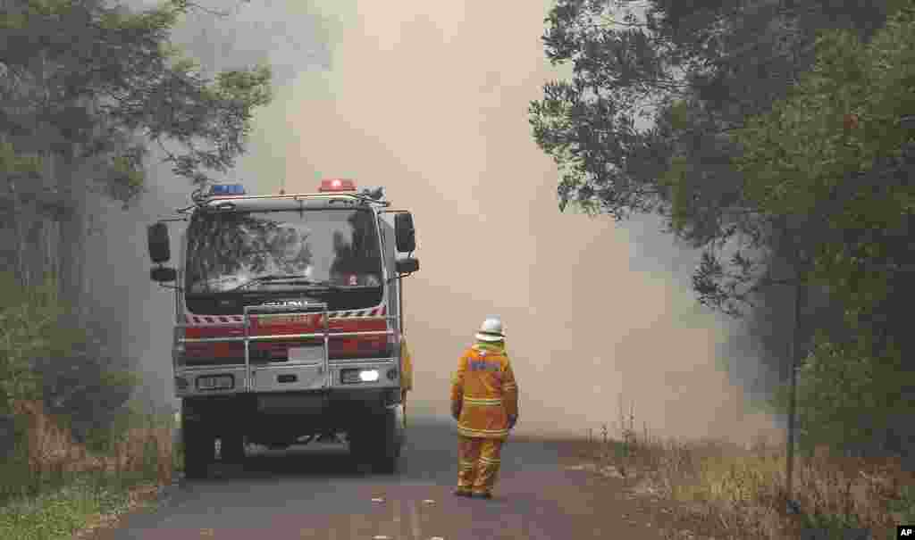 A firefighter watches as smoke covers a road in Bilpin, west of Sydney, Oct. 22, 2013.