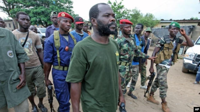 A man known as Commander Bauer, the chief of a group that calls itself the 'invisible commandos' and backs Alassane Ouattara, walks with his fighters in northern Abidjan's Abobo district, March 26, 2011