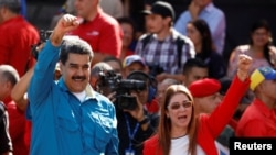 FILE - Venezuela's President Nicolas Maduro and his wife, Cilia Flores, greet supporters at a rally marking the 60th anniversary of the end of dictator Marcos Perez Jimenez's regime, in Caracas, Jan. 23, 2018.