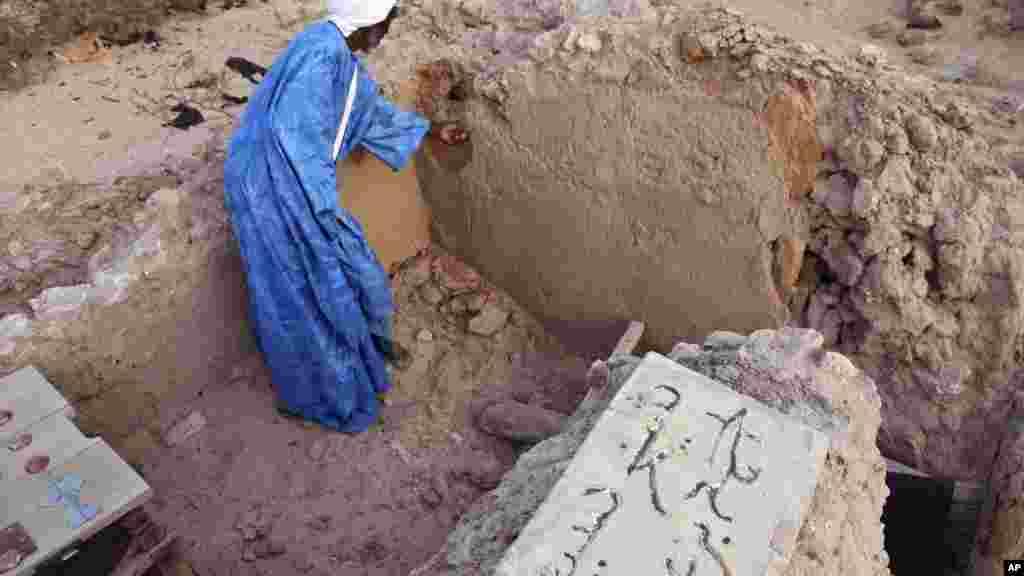 Le chef de maçon Alassane Ramiya examine une tombe après l'attaque à Tombouctou, au Mali, le 4 avril 2014.
