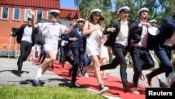 Para pelajar merayakan kelulusan dari SMA mereka seperti biasa di Stockholm, Swedia, Rabu (3/6).