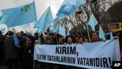 "Turks of Crimean Tatar origin waves Crimean flags and hold a banner that reads "" Crimea is the homeland of Crimean Tatars "" as they demonstrate to protest against Russia's military intervention in Crimea, Ukraine, in Ankara, Turkey, Sunday, March 2, 2014."