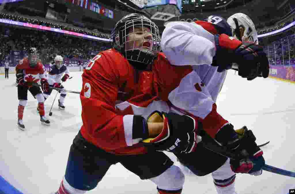 Laura Fortino do Canadá (8) leva com o cotovelo de Jocelyne Lamoureux dos Estados Unidos (17) no jogo de hóquei no gelo, para a medalha de ouro. O Canadá ganhou, Jogos Olímpicos de Inverno, Fev. 20, 2014.