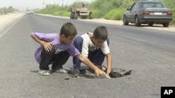 Two Iraqi boys dig in a hole created earlier by a landmine outside the town of Fallujah, 65 kilometers west of Baghdad, Iraq. (FILE)