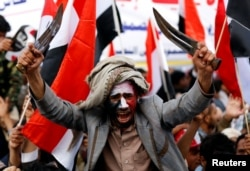 FILE - A man waves traditional daggers, or Jambiyas, as he attends with supporters of the Houthi movement and Yemen's former president Ali Abdullah Saleh a rally to mark two years of the military intervention by the Saudi-led coalition, in Sanaa, Yemen March 26,