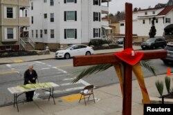 Seorang umat paroki mengambil daun palem di luar Gereja Katolik Sakramen Suci pada perayaan Minggu Palma di tengah wabah COVID-19 di Worcester, Massachusetts, 5 April 2020. (Foto: Reuters)