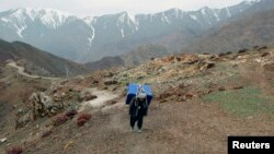 FILE - An Afghan man carries a ballot box on his back to polling stations which are not accessible by road in Shutul, Panjshir province, April 4, 2014. More than 100 people have died in avalanches in the region, local officials said, Feb. 25, 2015.