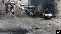 FILE - Syrian citizens gather near burned cars after airstrikes hit Manbij, in Aleppo province, Syria, in this undated image posted online on July 28, 2016, by supporters of the Islamic State militant group on an anonymous photo sharing website.
