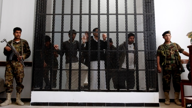 Yemeni soldiers stand guard as suspected al-Qaida militants, behind bars, attend a court hearing in Sanaa, Yemen, March, 4, 2013.