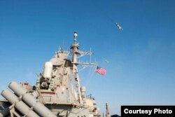 FILE - Image of Russian fly-over near guided-missile destroyer USS Donald Cook in Baltic Sea as provided by the U.S. Navy 6th Fleet.