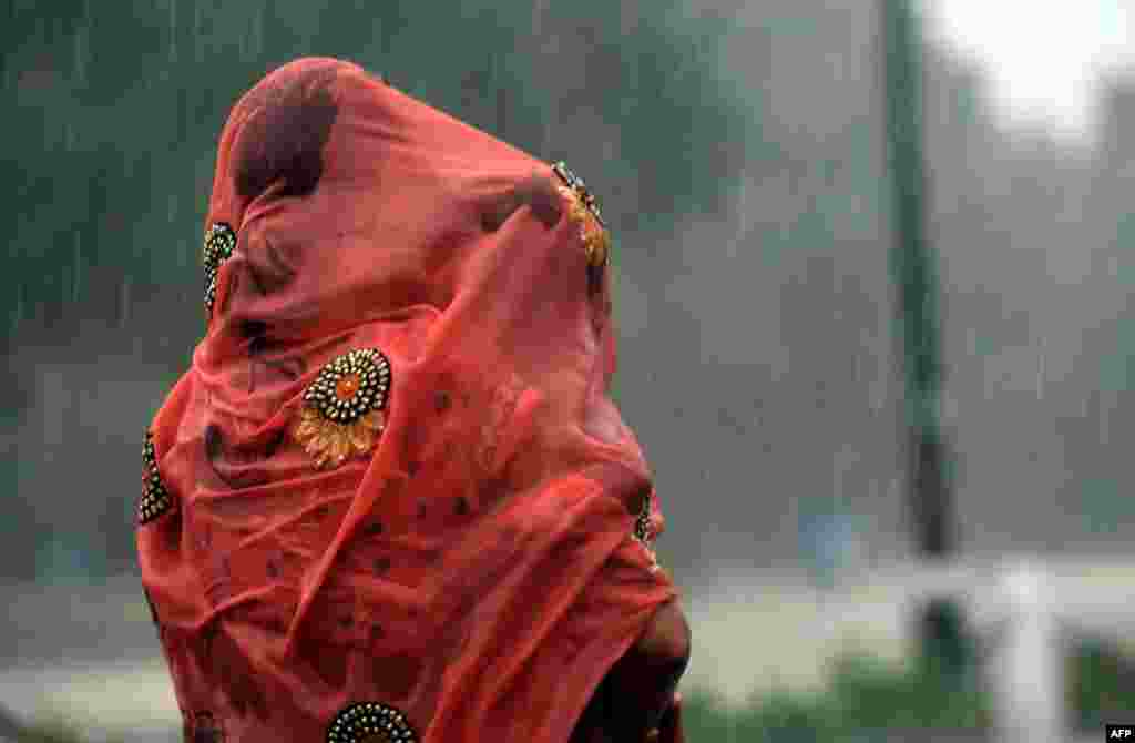 An Indian woman covers her baby under her saree during heavy rain at Rajpath in New Delhi.