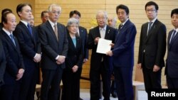 Perdana Menteri Jepang Shinzo Abe (tiga dari kanan) menerima petisi dari Shigeo Iizuka (tengah), pemimpin sekelompok keluarga Jepang yang diculik Korea Utara, di dampingi Sakie Yokota (sebelah kirinya) ibu dari Megumi Yokota, salah seorang korban penculikan Jepang dan anggotanya di kediaman resmi Abe di Tokyo, Jepang, 30 Maret 2018. (Foto: dok).
