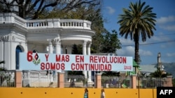 People walk past a banner hung to honor the Jan. 1, 2019, celebration of the 60th anniversary of the Cuban revolution in Santiago de Cuba, Cuba, Dec. 31, 2018.