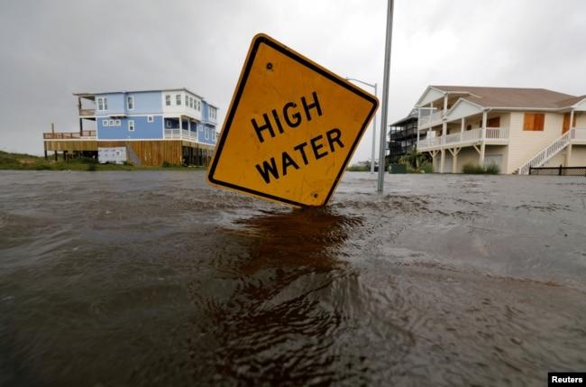 El agua casi alcanza una señal de alerta de inundación parcialmente doblada por el huracán Florence en Oak Island, Carolina del Norte, el 15 de septiembre de 2018.