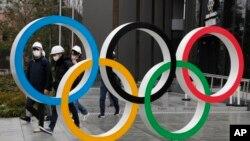 Warga yang mengenakan masker berjalan dekat Cincin Olimpiade di Stadion Nasional di Tokyo, Jepang (foto: dok).