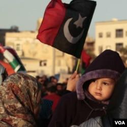 Seorang perempuan Libya menggendong bayinya dalam unjuk rasa anti-Gaddafi di Benghazi (22/3).
