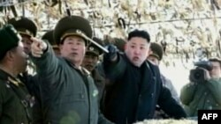 Pemimpin Korut, Kim Jong-un (tengah) tengah menunjuk ke arah sebuah pulau di Korsel saat meninjau latiham artileri di pulau Wolnae dekat perairan sengketa (12/3).