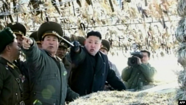 Screen grab shows North Korean leader Kim Jong-Un (C) pointing to a South Korean island during a trip to an artillery unit on Wolnae Island near the disputed maritime frontier with South Korea, March 12, 2012.