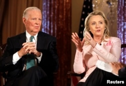 """FILE - Then-Secretary of State Hillary Clinton speaks next to former Secretary of State James Baker during a """"Conversation on Diplomacy"""" at the State Department in Washington, June 20, 2012."""