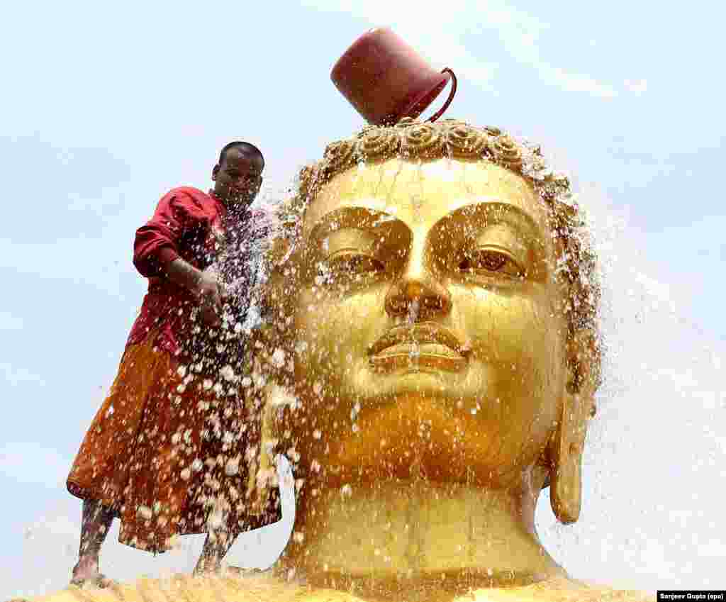 A Buddhist monk cleans the statue of Lord Buddha ahead of his birth anniversary in a monastery in Bhopal, India.