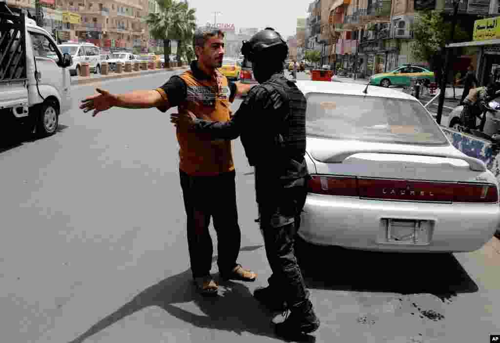 Dengan meningkatnya langkah keamanan, polisi federal Irak melakukan pemeriksaan di sebuah pos di Baghdad (11/6). (AP/Karim Kadim)