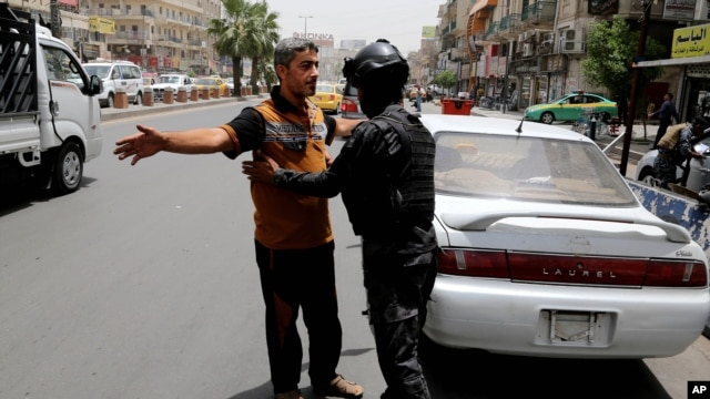 With tightened security measures, an Iraqi federal policeman conducts a search at aBaghdad checkpoint on June. 11, 2014.